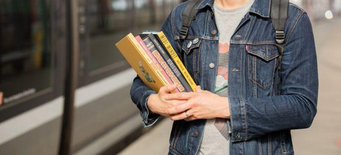 Client sur un quai avec plusieurs livres dans les mains